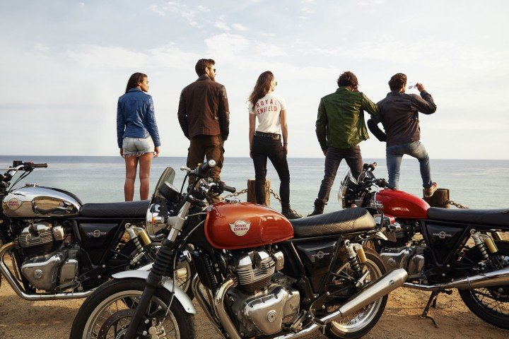 group of friends standing next to their royal enfield interceptor 650 motorcycles and looking out over the ocean